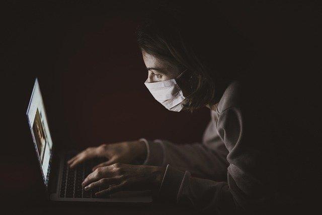 Persona delante de un ordenador con una mascarilla | Foto: PIXABAY